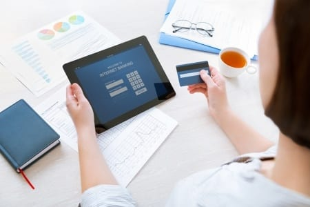 Stock image of women holding iPad and credit card