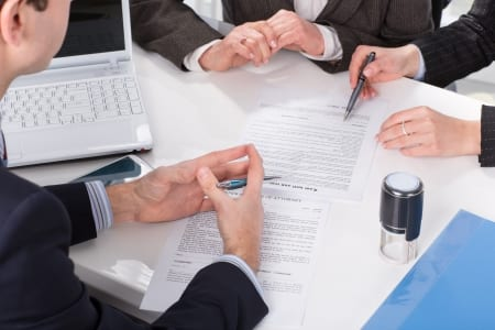 stock image of business people reviewing contract