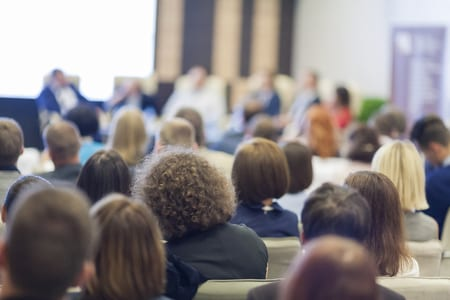 Stock image of crowd sitting in conference room