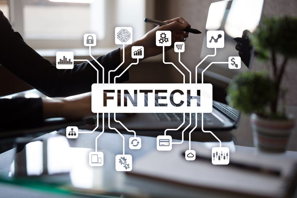 "Image of person using a pointing device on laptop screen with the words ""Fintech"" overlaid."